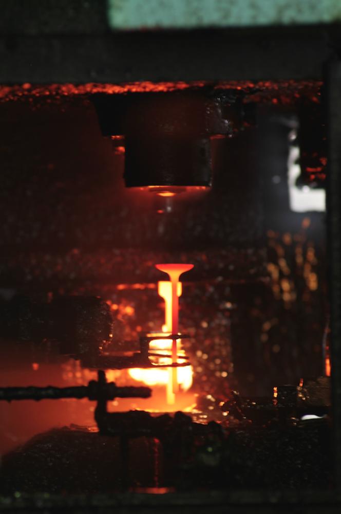 Forgiatura di una valvola in acciaio speciale ad alto tenore di cromo e nichel in uno stabilimento Eaton. L'operazione si effettua sotto una pressa, a una temperatura superiore a 1000 °C