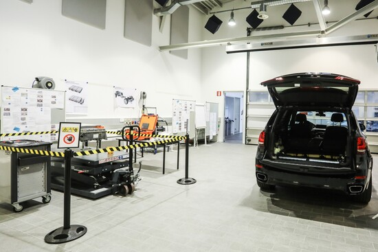 BMW X5 ibrida con batteria estratta, dal fondo vano bagagli e riposta in area lavoro