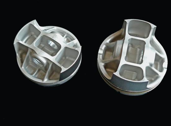 """I pistoni dei motori aspirati da competizione (e anche quelli di alcuni motori di serie di prestazioni molto elevate) hanno il disegno """"box-n-box"""" ben visibile in questa immagine. Sono ottenuti per stampaggio a caldo, in una lega di alluminio che in molti casi è a elevato tenore di rame"""