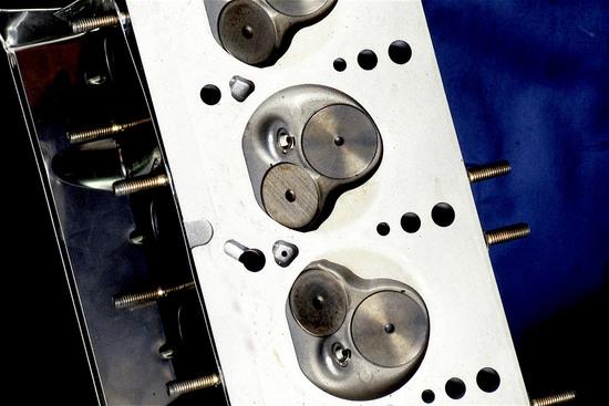 La foto mostra una testa con camere di combustione aventi una conformazione intermedia tra quella a scatola di sardine e quella polisferica. Le valvole non sono parallele ma leggermente inclinate tra loro